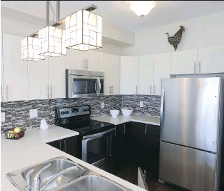 ?? PHOTOS: JEAN LEVAC/OTTAWA CITIZEN ?? Upgrades in the Beringer kitchen include the backsplash, eating bar and stained-glass light fixture, plus the U-shaped configuration.