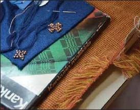 ??  ?? MÅNGA DETALJER. Fåll gjord genom brickvävning och bronsspiraler på blått tyg.