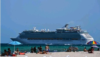 ?? — AFP file photos ?? A cruise ship sails in the background as people relax in Miami Beach, Florida.