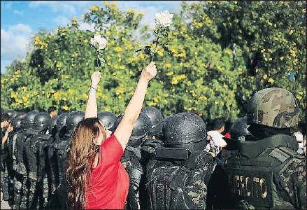 ?? GUSTAVO AMADOR / EFE ?? Una simpatizante de la oposición enseñando flores ante la policía, ayer en Tegucigalpa