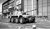 ?? PHOTO: REUTERS ?? A military tank patrols near a shopping centre which was damaged after several days of looting in Durban