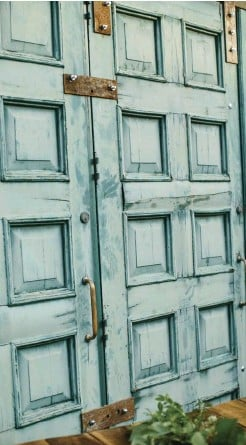 """??  ?? top right: THESE COLORFUL DOORS, which came off a church in Chattanooga, pop in turquoise blue. Mandi and Oliver painted them, """"adding some color to the brick, concrete exterior."""""""