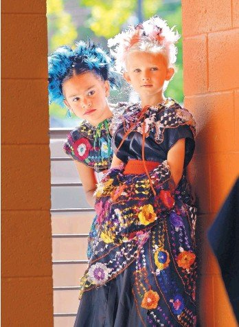 ?? JIM THOMPSON/JOURNAL ?? From left, Danya Narlesky, 6, and Gemma Keim, 8, watch from the wings of the stage as other dancers in Los Niños de Santa Fe y Compania perform at Villa Hispana at the New Mexico Stat e Fair on Saturd ay.