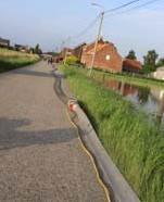 ?? FOTO WARD BOSMANS ?? De brandweer legde over een afstand van 1.200 meter slangen om het water weg te pompen richting Leest-centrum.