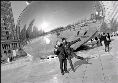 ??  ?? Xavier Canas and Cari Del­gado pose in front of Cloud Gate (the Bean) while tour­ing down­town with John Os­bolt. Os­bolt has been a Greeter since the pro­gram be­gan in Chicago in 2002.