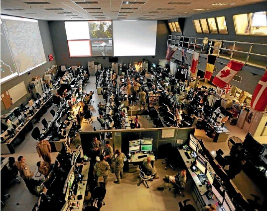 ??  ?? The centerpiece of the CAOC is a bunker-like building with rows of desks and computer stations and screens.