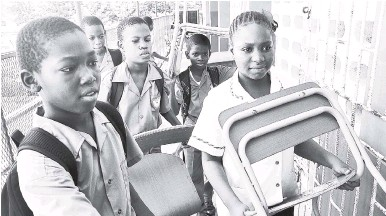 ?? FILE ?? Grade-six students at Rousseau Primary School in the Corporate Area take in new desks and chairs to their classroom. Schools need auxiliary fees to provide these items in time for the start of the new school year.