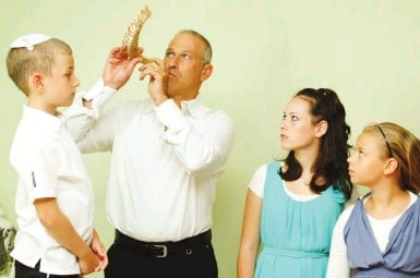 ?? (Mendy Hechtman/Flash90) ?? A MAN blows a shofar for his family, as is customary every morning during the month of Elul.