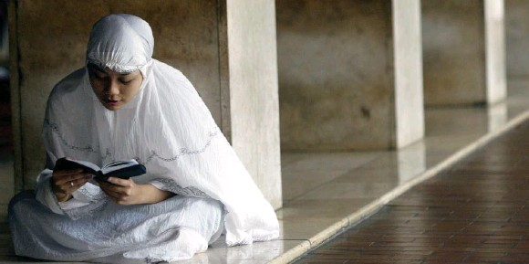 ?? TATAN SYUFLANA/THE ASSOCIATED PRESS ?? Mainstream scholars say the Qur'an does not rule that women are inferior to men, although conservatives sometimes disagree. A woman reads the Qur'an in Jakarta, Indonesia.