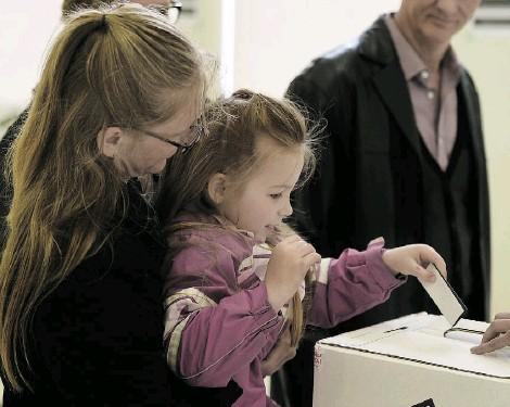 ?? JOHN LUCAS/ EDMONTON JOURNAL ?? Jasmine Wronko, 5, helps her mother Cheri Harris vote on Wednesday in an advance poll at McKernan Community Hall.