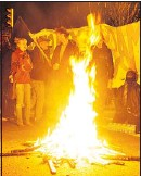 ?? IAN LINDSAY — PNG FILES ?? Protesters gather around a fire set on Commercial Drive on Tuesday.