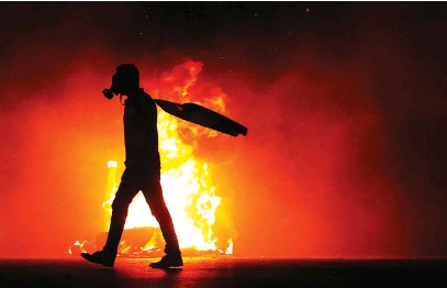 ?? Picture: AFP ?? FLARE-UP. A Palestinian protester walks by a burning tyre amid clashes with Israeli security forces at the Hawara checkpoint, south of Nablus city, in the occupied West Bank on Saturday.
