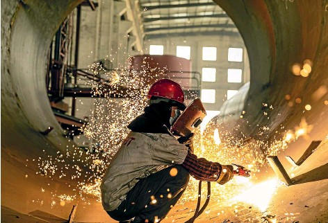 ?? GETTY IMAGES ?? A welder works in a workshop of an equipment manufacturing enterprise to produce large building materials equipment for export to countries along the ''One Belt And One Road'' route, in Hai 'an, east China's Jiangsu Province.