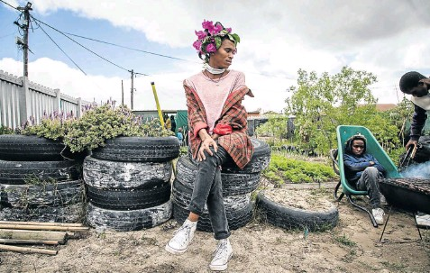?? Picture: Ian Skene ?? Be sure to wear some flowers in your hair when celebrating Garden Day — as Azola Khala did in Khayelitsha, Cape Town, last year. Asange Fongoqa looks on from his wheelbarrow seat.