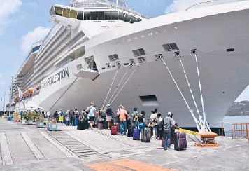?? ORVIL SAMUEL/AP ?? To the rescue: British, Canadian and U.S. nationals line up alongside the Royal Caribbean cruise ship Reflection to be evacuated free of charge on Friday from Kingstown on the eastern Caribbean island of St. Vincent. La Soufriere volcano shot out another explosive burst of gas and ash Friday morning as the cruise ship arrived.