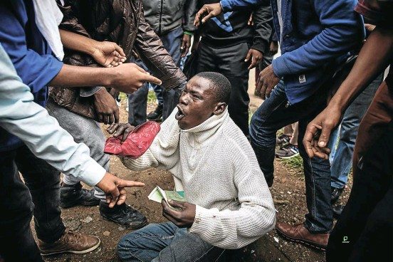 ?? Picture: James Oatway ?? A terrified man begs for his life. He was saved from the mob only after producing his South African identity document. An 'anti-crime march' had turned into an anti-migrant hunt. 'We are the barbarians,' writes political commentator Justice Malala in one of the accompanying essays.