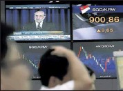 ?? AHN YOUNG-JOON / ASSOCIATED ORESS ?? Currency traders at the Korea Exchange Bank in Seoul work in front of a TV showing Ben Bernanke. Asian stock markets fell Thursday after reports the U. S. Federal Reserve said it could start scaling back its economic stimulus program.