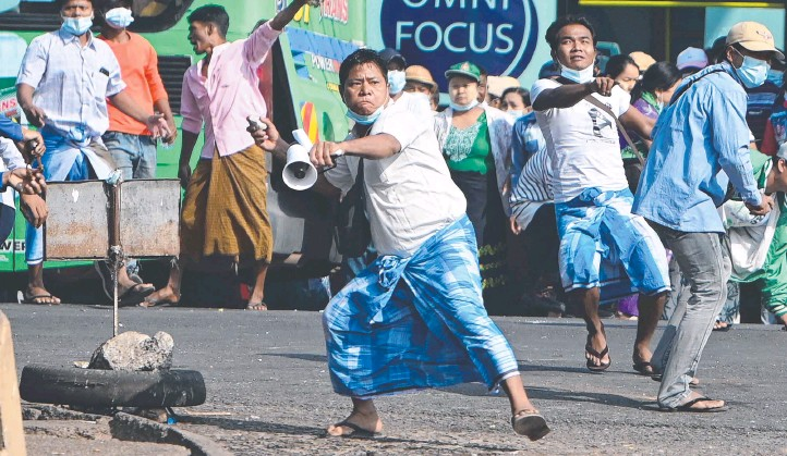 ??  ?? A pro-military supporter throws stones at pro-democracy residents in Yangon, following weeks of mass demonstrations against last month's military coup in Myanmar. Picture: AFP