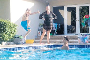 ??  ?? Deanna Peysekhman, watches her son, Nate, left, and nephewDeni­sTrifonov at herparents'pool in Hollywood onThursday­The Peysekhman­s, of Freehold, NewJersey are staying in South Florida at least through mid-January.