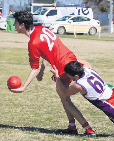 ??  ?? ■ RIGHT: Blighty's Kane Morris gets his handball away despite the efforts of Jerilderie's Brody Benjamin in the thirds. Photo courtesy Sally Simpson.