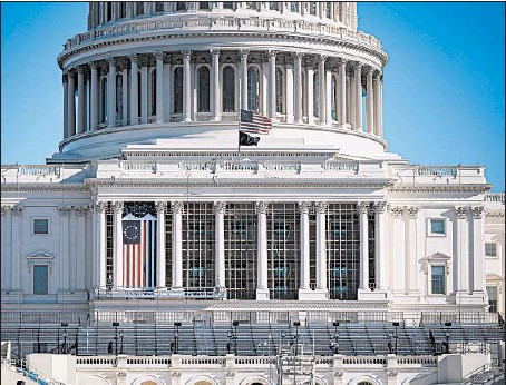 ?? AL DRAGO/GETTY ?? The flag flies at half-staff in honor of a slain Capitol Police officer as construction continues for the inauguration on theWest Front of the U.S. Capitol.