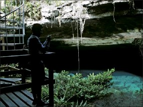 ??  ?? A visitor pauses to take a photo in a cave, partially lit by sunlight, in Lucayan National Forest on Grand Bahama.