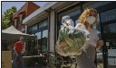 ?? DAMIAN DOVARGANES — THE ASSOCIATED PRESS ?? Fashion designer Josie Vand wears a facemask as she retrieves a bag with organic vegetables from a farm box from County Line Harvest in Los Angeles on Friday.