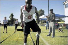 ??  ?? NFL running back and Horn Lake High School alumnus Brandon Jackson cheers on Michael Daughiry as he works through an obstacle course at Jackson's camp. BRANDON DILL SPECIAL TO THE COMMERCIAL APPEAL