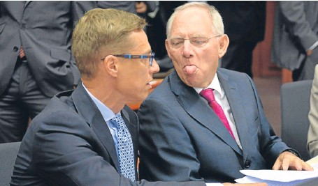 ?? Picture: Getty Images. ?? German finance minister Wolfgang Schauble sticks his tongue out at Finnish finance minister Alexander Stubb during the Brussels bailout talks.