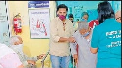 ?? HT PHOTO ?? Volunteers give a helping hand to an elderly to get vaccinated.