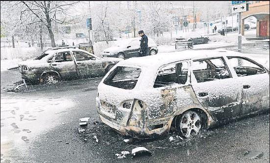 ?? TT NEWS AGENCY / REUTERS ?? Un policia inspecciona un cotxe incendiat a Rinkeby, un suburbi d'Estocolm