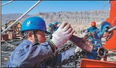 ??  ?? Electricians with State Grid Xinjiang Electric Power work on a power transmission tower in the Xinjiang Uygur autonomous region in September. Employees of State Grid Xinjiang Electric Power work on an engineering project in Aksu, Xinjiang, in October.