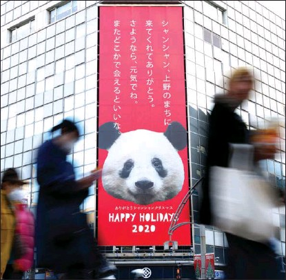 ?? NAOKI NISHIMURA / AFLO ?? A billboard in Tokyo, Japan, on Dec 9 advertises a thank-you celebration for female giant panda Xiang Xiang, a popular attraction at Tokyo's Ueno Zoological Gardens. The panda had been set to return to China this month but instead will stay until May because of the pandemic.