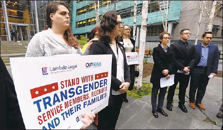 ?? Elaine Thompson Associated Press ?? PLAINTIFFS Cathrine Schmid, second left, and Conner Callahan, second right, listen with supporters in March at a federal courthouse in Seattle, where a judge ordered President Trump not to take any action barring transgender troops from serving in the military.