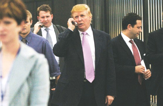 """?? CYRUS MCCRIMMON/DENVER POST ?? Donald Trump, center, walks outside of a business convention in Loveland, Colo., in 2005. Felix Sater is at right, wearing a red tie. In sworn testimony in 2013, Trump said that if Sater """"were sitting in the room right now, I really wouldn't know what he looked like."""" Watch a video of Trump's 2013 deposition at wapo.st/TrumpSater."""