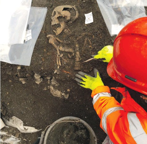 ?? AFP PHOTO/CROSSRAIL ?? A researcher unearths one of about 3,000 skeletons buried in London's Bedlam cemetery, which is destined to become a new train station.