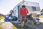 ?? Jessica Christian / The Chronicle ?? Amilee Smith, 60, cleans up the area outside of her RV with her dog Mimi while parked at an RV encampment along Rydin Road in Richmond.
