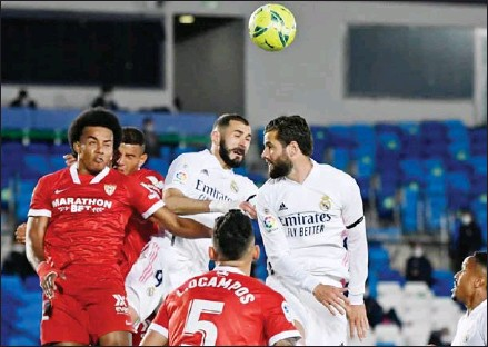 ?? AFP ?? Real Madrid's French forward Karim Benzema (centre) and Real Madrid's Spanish defender Nacho Fernandez (right) jump for the ball with Sevilla's French defender Jules Kounde (left) during the Spanish League football match on May 9.