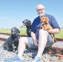 """?? ALL PHOTOS BY SHARON MONTGOMERY-DUPE ?? Former reality television contestant Richard Hatch, winner of the first """"Survivor"""" series in 2000, relaxes in a field in Sydney in June 2017 with his dogs. Currently 11 of the more than 20 properties Hatch snapped up across the Cape Breton Regional Municipality during earlier municipal property sales are featured in the current CBRM tax sale."""