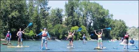 ?? Courtesy, Undercurrents ?? Participants in an Undercurrents group lesson on the Bow River raise their paddles in a show of enthusiasm.