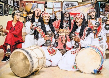 ?? YASSINE ALAOUI ISMAILI FOR THE NEW YORK TIMES ?? Abdellah El Gourd, third from right, performing traditional Gnawa music in Tangier in August.