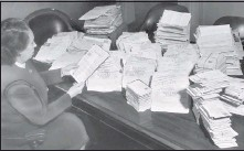 ?? STAFF PHOTO ?? Mrs. Thurman B. Towill, of Gov. John S. Battle's office, looks at stacks of protests in the Martinsville case. Battlewas governor from1950-1954.