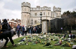 ?? CHRIS J RATCLIFFE Getty Images ?? People arrive at Windsor Castle throughout the day on Saturday to leave floral tributes and hand-written notes to Prince Philip, who died Friday, in Windsor, United Kingdom.