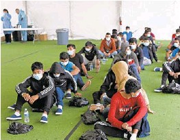 ?? DARIO LOPEZ-MILLS/AP ?? Young migrants wait to be tested for COVID-19 last month at the Department of Homeland Security holding facility in Donna, Texas. Officials are scrambling to handle a huge spike in children crossing the U.S.-Mexico border alone.
