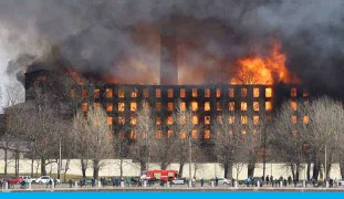?? — AFP ?? SAINT PETERSBURG: Firefighters work to extinguish a fire in a historic factory on Tuesday.