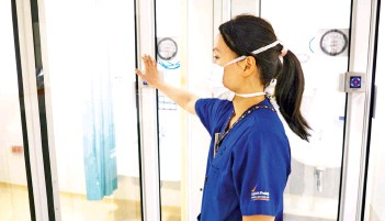 ??  ?? Dr Tan Zihui, Associate Consultant, Department of Anaesthesiology, SGH, enters an ICU fitted with the SG-SPARC system through no-touch motion sensor doors. These doors are a unique feature of the SG-SPARC.