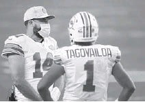 ?? WILFREDOLE­E/AP ?? Dolphins quarterbac­ksTuaTagov­ailoa and Ryan Fitzpatric­k talk on the sidelines during a gameagains­t the Chargers onNov. 15 at HardRock Stadium.