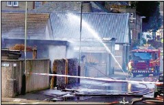 ??  ?? EXPLOSION: Firefighters tackle the fire at the garage in Monifieth.