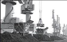 ?? WANG CHUN / FOR CHINA DAILY ?? A large ship unloads iron ore at a port in Lianyungang, Jiangsu province.