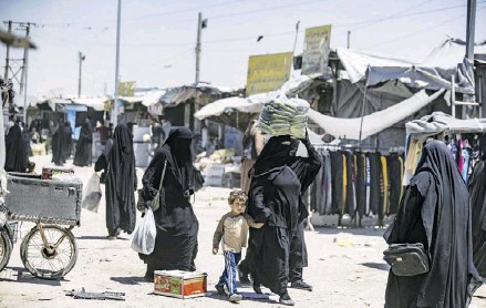 ??  ?? Women and children walk through the al-Hawl refugee camp in northeastern Syria, which houses relatives of suspected Islamic State fighters, on June 23, 2021. Ukrainian woman Amina and her children spent two years in al-Hawl in dire living conditions before being evacuated to Ukraine on June 16, 2021.